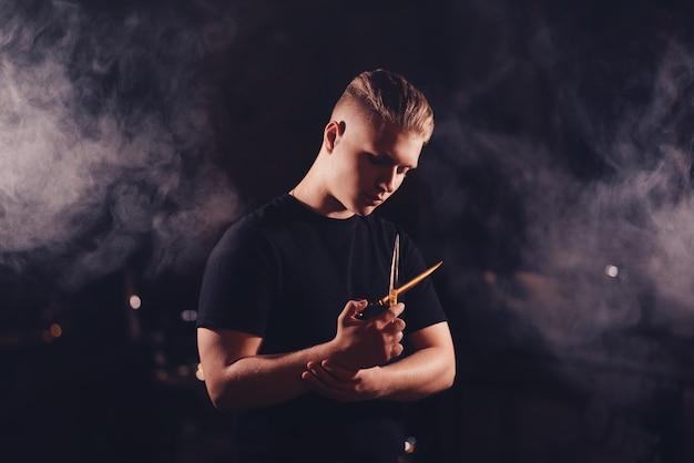 Guy friseur posiert mit schere und rauch