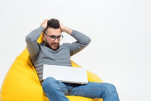Guy frustriert, während er auf einem gelben hocker sitzt