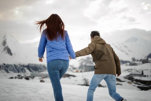 Guy führt ein mädchen zu einem spaziergang in richtung der schneeberge