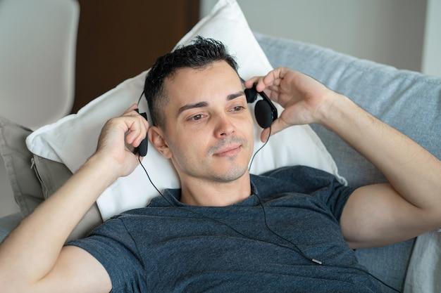 Guy genießt die musik, während er mit kopfhörern auf der couch liegt
