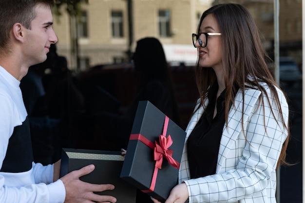 Guy gibt dem überraschten mädchen ein geschenk. alles gute zum geburtstag, valentinstag.