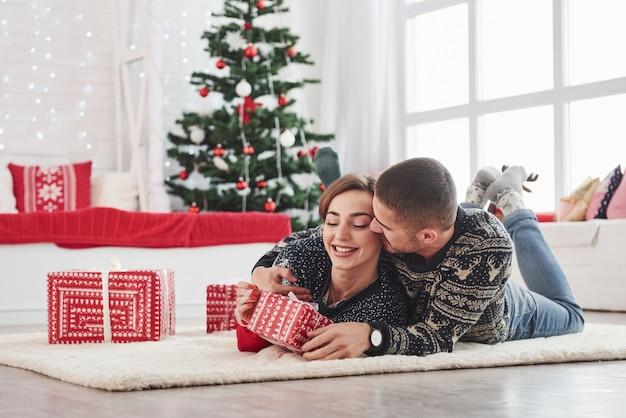 Guy gibt seiner frau weihnachtsgeschenk. reizende junge paare, die auf dem wohnzimmer mit grünem feiertagsbaum am hintergrund liegen