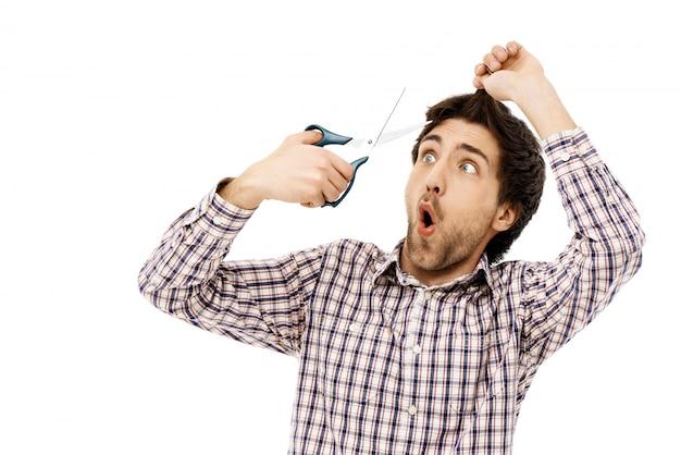 Guy hält eine schere, schneidet haare in selbstquarantäne
