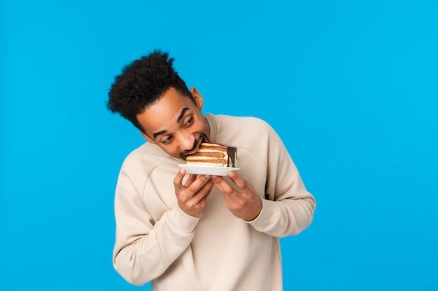 Guy hat stück kuchen gestohlen und es schnell gegessen. lustige und nette afroamerikanermannhalteplatte, köstlicher nachtisch des bisses, der geburtstag, das geschmackvolle lebensmittel der feiertage genießend feiert und stehen blau