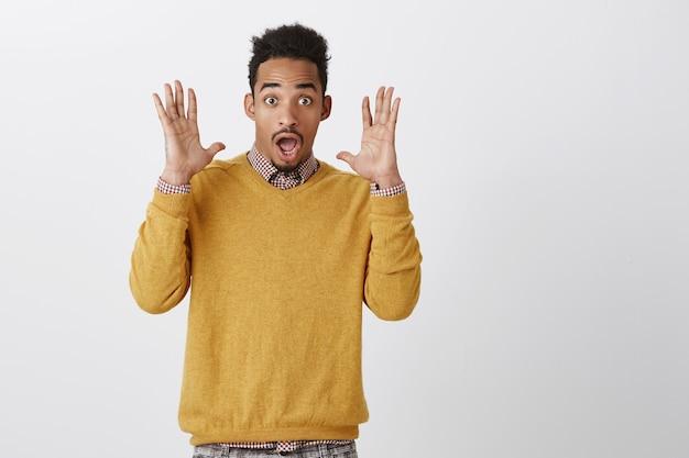 Guy hatte angst vor einem nicht erwarteten knall. porträt eines attraktiven lustigen afroamerikaners mit afro-frisur, die palmen nahe gesicht erhebt, vor überraschung und erstaunen schreit, kiefer fallen lässt und nach luft schnappt
