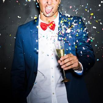 Guy in abendjacke mit glas zwischen konfetti werfen
