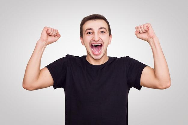 Guy in einem schwarzen t-shirt freut sich über den sieg