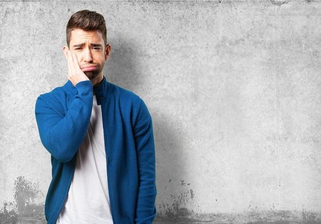 Guy in einer blauen jacke mit zahnweh
