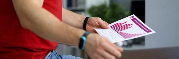 Guy in jeans analysiert finanzbericht diagramm. statistiken für gegebene szenarien führen generator. geschäftsführung. informationen zur kundenbindung. investitionskosten. potenzielle wettbewerber