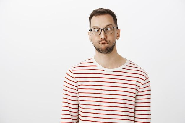 Guy kann nicht erwachsen werden. porträt des lustigen verspielten europäischen mannes mit der borste in den gläsern, die schielen und nase betrachten