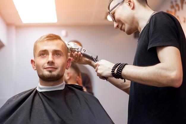 Guy lässt sich in einem friseurladen die haare schneiden