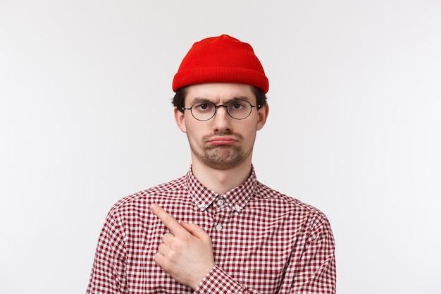 Guy missbilligt langweilige party, drückt abneigung aus. skeptischer niedlicher kaukasischer mann in der roten mütze und in den gläsern