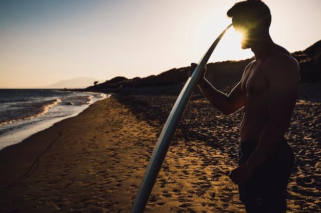 Guy mit surfbrett bei sonnenuntergang