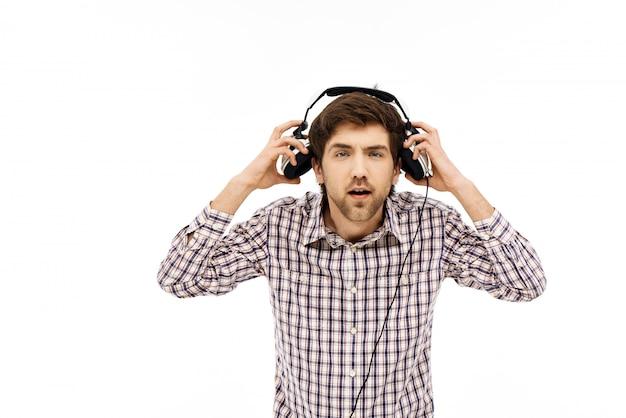 Guy nimmt kopfhörer ab, um zu hören, was sie fragen