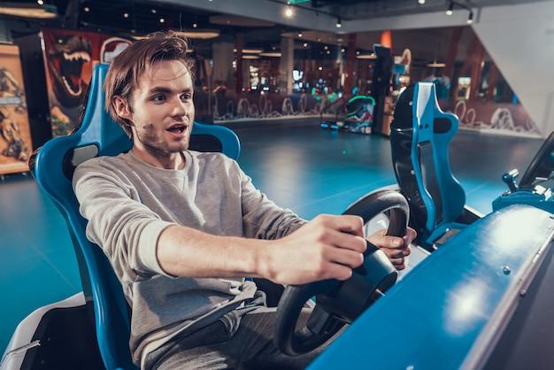 Guy reiten auto in der spielhalle. der mensch ist glücklich, spiel zu spielen.