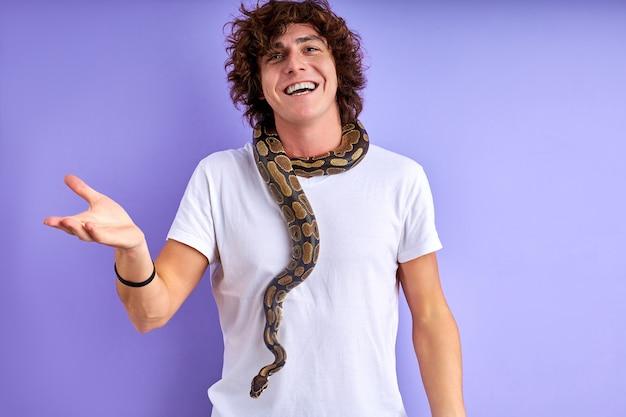 Guy steht mit schlange am hals, er ist mutig, hat keine phobie, spricht und lächelt. isolierter lila hintergrund