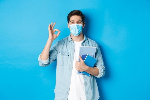 Guy student in der medizinischen maske, die glücklich schaut, notizbücher hält, ok zeichen zeigt, über blauer wand stehend