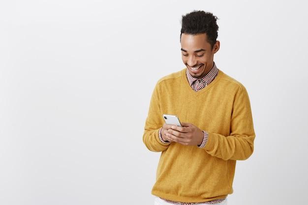 Guy traf ein lustiges mädchen in einem sozialen netzwerk. porträt des erfreuten glücklichen afroamerikanischen mannes, der breit lächelt, während er auf den bildschirm des smartphones schaut, nachricht schreibt oder lustiges video sieht