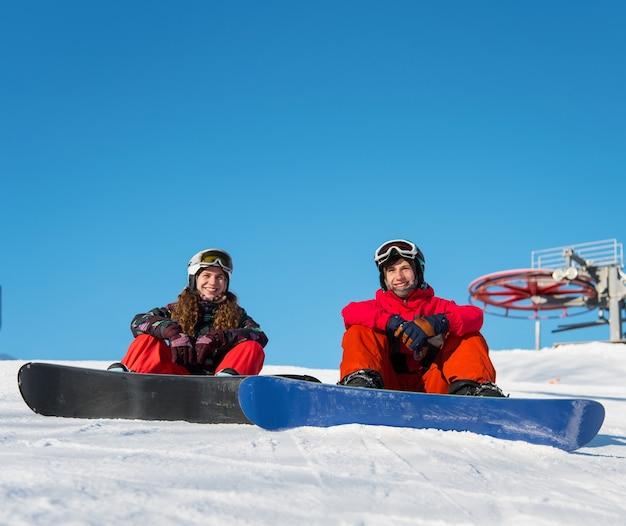 Guy und girl snowboarder auf dem schnee