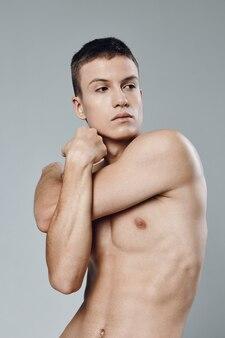 Guy verdrehte seine arme auf einem grauen hintergrund nackter oberkörper muskeln bizeps bodybuilding fitness
