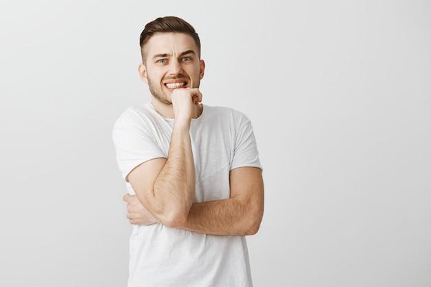 Guy zuckt zusammen, als er etwas ekelhaftes oder schmerzhaftes sieht, das sich unbehaglich verzieht
