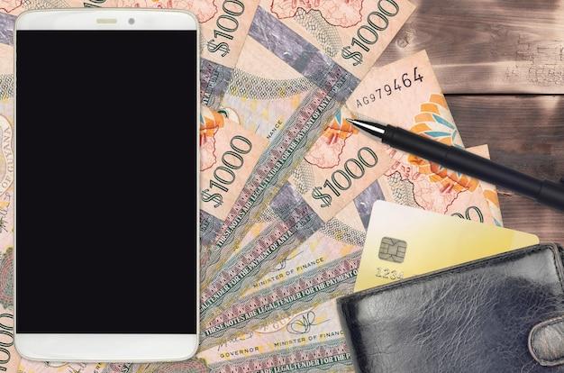 Guyanese dollarnoten und smartphone mit geldbörse und kreditkarte