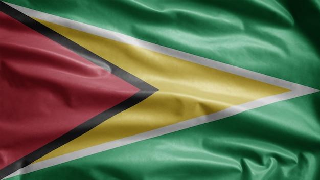 Guyanesische flagge weht im wind. nahaufnahme von guyana banner weht, weiche und glatte seide. stoff textur fähnrich hintergrund. verwenden sie es für das konzept für nationalfeiertage und länderanlässe.