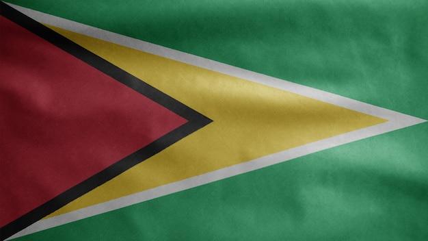 Guyanesische flagge weht im wind. nahaufnahme von guyana banner weht, weiche und glatte seide. stoff textur fähnrich hintergrund.