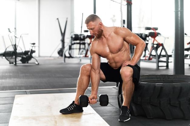 Gym athlet bizeps übung hantel muskulösen mann sitzen rad halten lift langhantel.