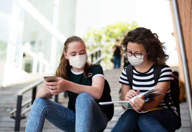 Gymnasiasten im neuen normalen lernen auf der treppe