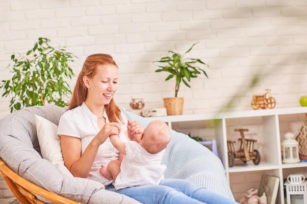 Gymnastik baby. frau, die übungen mit baby für seine entwicklung tut.