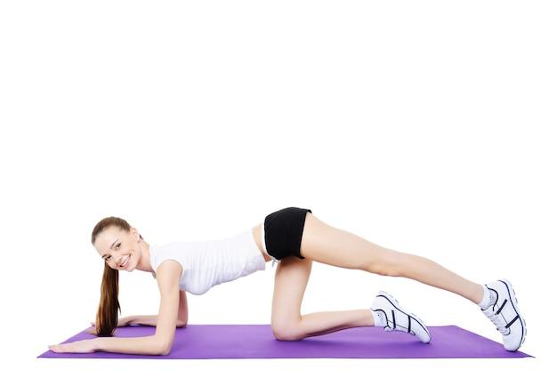 Gymnastik des jungen mädchens auf dem turnteppich - isoliert