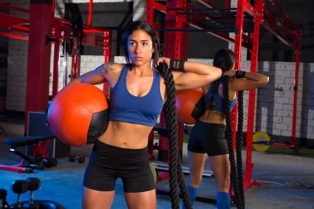 Gymnastikfrau mit belastetem ball und seil