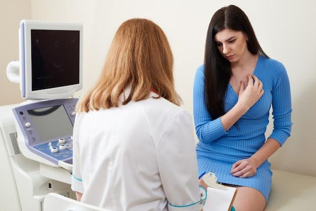 Gynäkologe berät junge frau im ultraschall-scan-büro