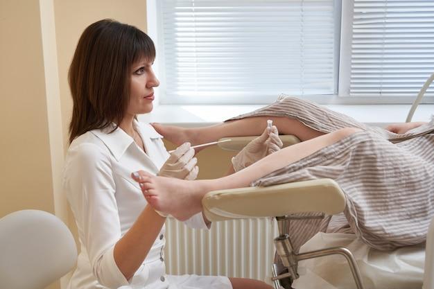 Gynäkologe, der eine vaginale untersuchung und tests der im stuhl liegenden patientin durchführt