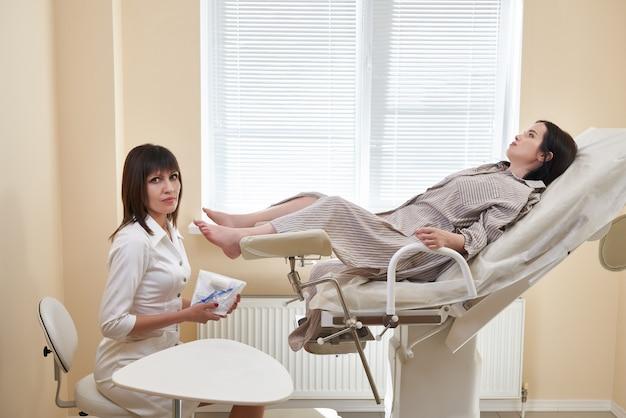 Gynäkologe, der einen spiegel für die vaginale untersuchung der patientin hält