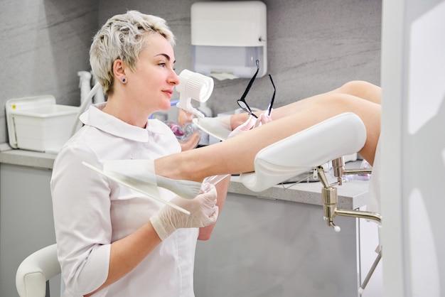 Gynäkologe mit vaginalspekulum in der klinik vor der untersuchung des patienten