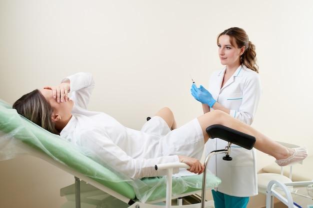 Gynäkologe untersucht eine patientin, die auf einem gynäkologischen stuhl sitzt