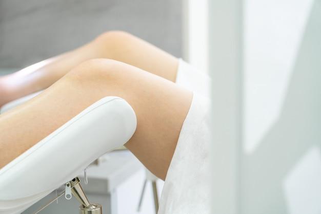 Gynäkologischer raum mit stuhl und ausrüstung. frauenbeine auf einem stuhl