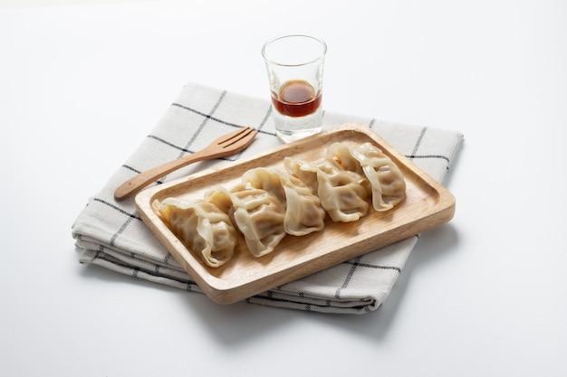 Gyoza auf hölzerner platte mit gabelholz und sojasoße. japanisches lebensmittel