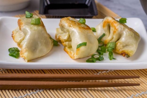 Gyoza ist ein traditionelles gericht der asiatischen küche mit pasta mit füllung aus rindfleisch, schweinefleisch oder gemüse