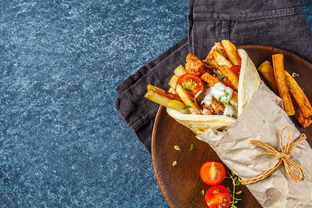 Gyros-souvlaki-wraps in pitabrot mit hähnchen, kartoffeln und tzatziki-sauce.