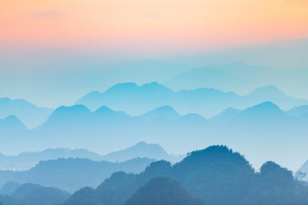 Ha giang karst geopark landschaft in nordvietnam. bergschattenbild atemberaubender landschaftsnebel und nebel in den tälern bei sonnenuntergang. ha giang motorradschleife, berühmte reiseziel biker einfache fahrer.