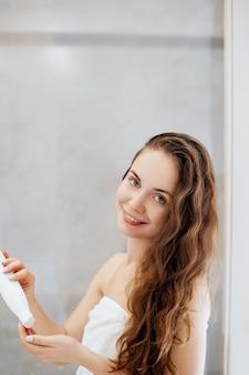 Haar. schöne junge frau, die lotion für haar anwendet und lächelt, während sie vor dem spiegel im badezimmer steht. pflege haare und haut. mädchen verwendet schutz feuchtigkeitscreme.