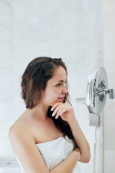 Haar- und körperpflege. frau, die nasses haar berührt und lächelt, während sie in den spiegel schaut. porträt des mädchens im badezimmer, das conditioner und öl anwendet. porträt der frau verwendet schutzfeuchtigkeitscreme.