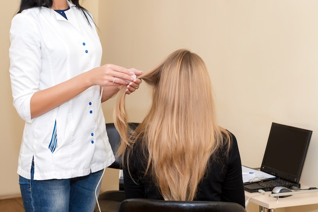 Haararzt, der haar überprüft. doktor überprüfen geduldiges weibliches haar einen speziellen apparat und einen computer.