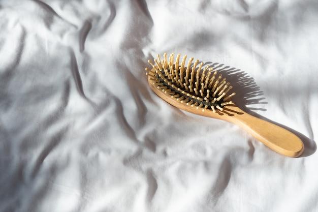 Haarausfall, haarausfall problem. hölzerner brauner kamm mit haarausfall auf weißer bettdecke.