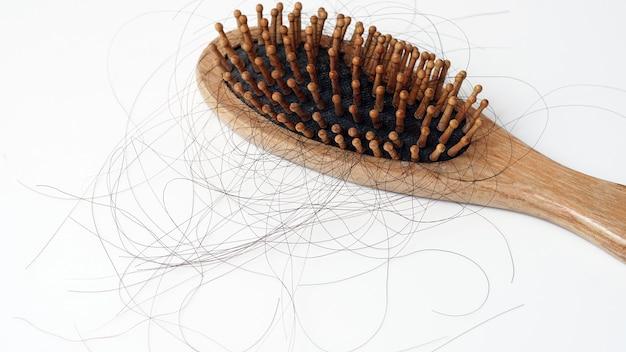 Haarausfall haftet an kammhaarausfall ernste probleme und haarausfall auf weißem hintergrund