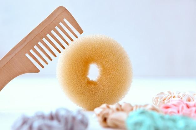 Haarbürstenschwamm aus holz und viele bunte seidenhaargummis friseurwerkzeuge und haargummis