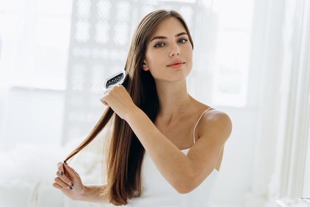 Haare bürsten. porträt der jungen frau, die gerades natürliches haar mit kamm bürstet. taille oben des mädchens, das schöne lange gesunde haare mit haarbürste kämmt. haarpflege- und beautykonzept